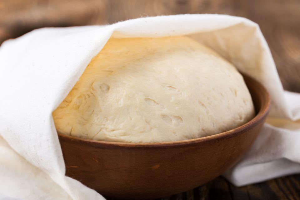 Raw yeast dough in rustic ceramic bowl