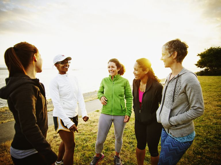 Female friends laughing together after run in park