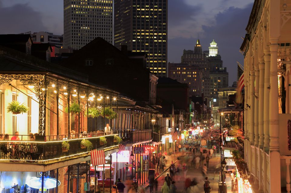 Night view of Bourbon street with downtown buildings in the background.