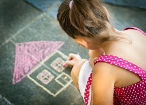 Little girl drawing a house on the sidewalk in chalk