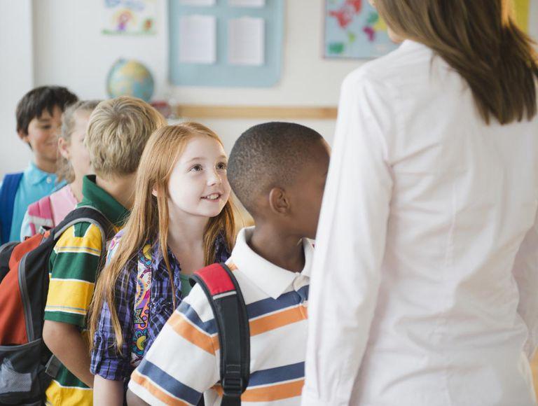 School children (8-9) with female teacher standing in row in classroom