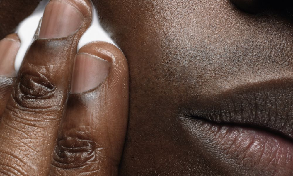 Man applying cocoa butter to his face.