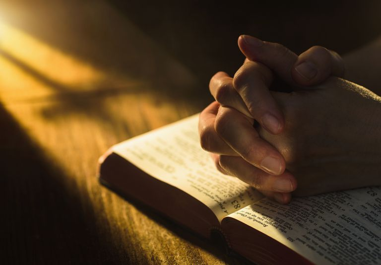 Close up of hands clasped on open Bible