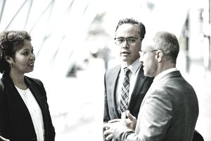 Three colleagues in discussion in corridor