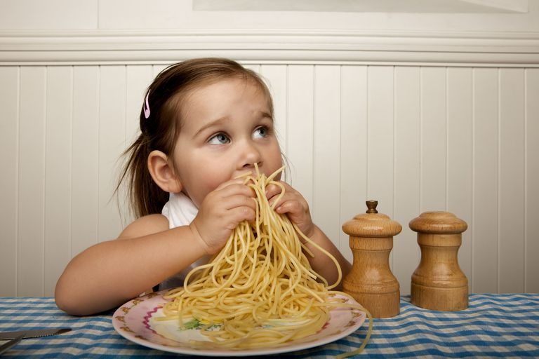 Little girl eating spaghetti with her hands