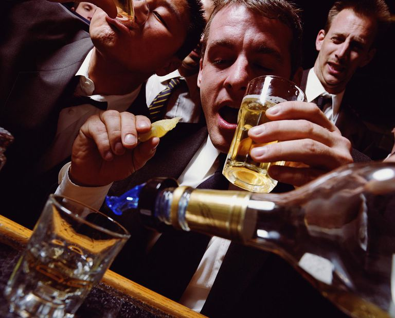 Businessmen having drinks at bar, man holding glass and slice of lime