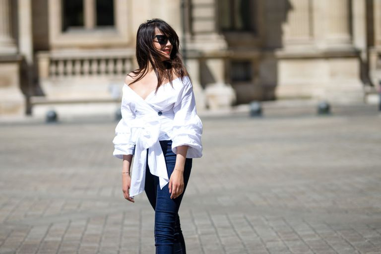 French street style woman's fashion outfit in jeans and an off the shoulder top