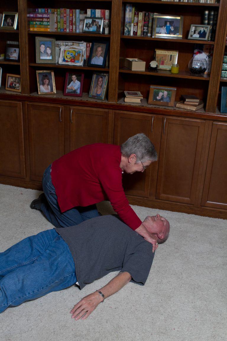 woman shaking an unconscious man