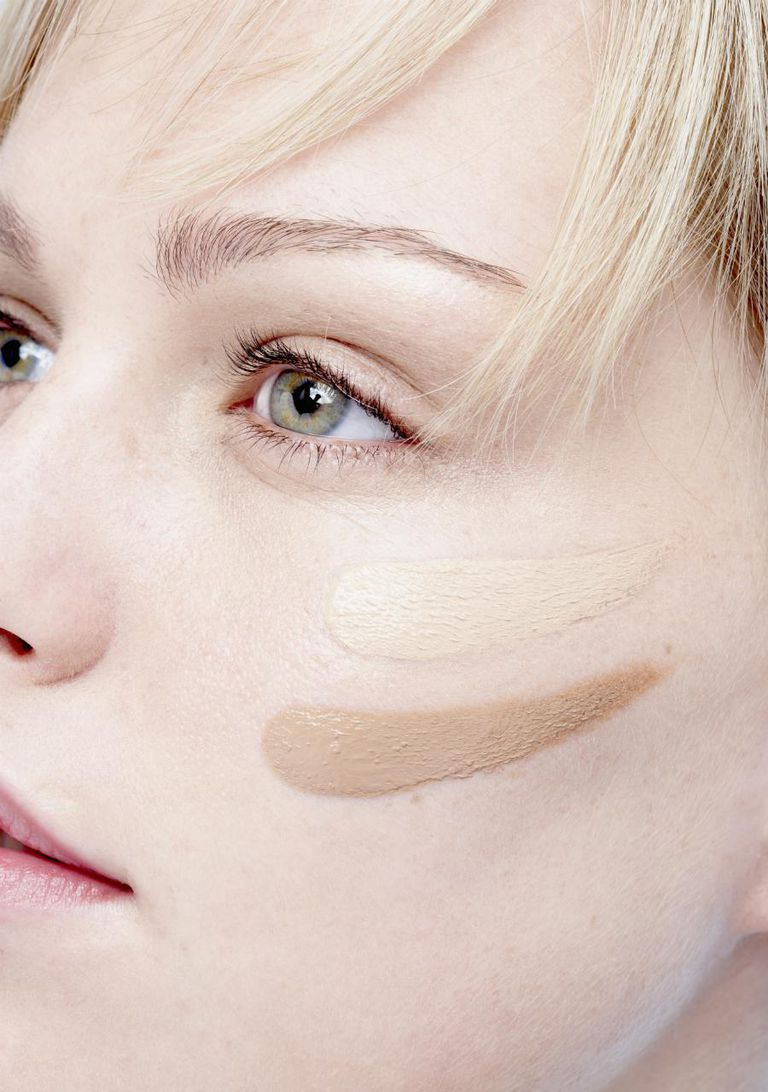Young woman with two shades of foundation on cheek