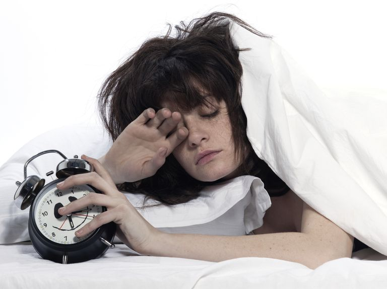 woman in bed tired with alarm clock