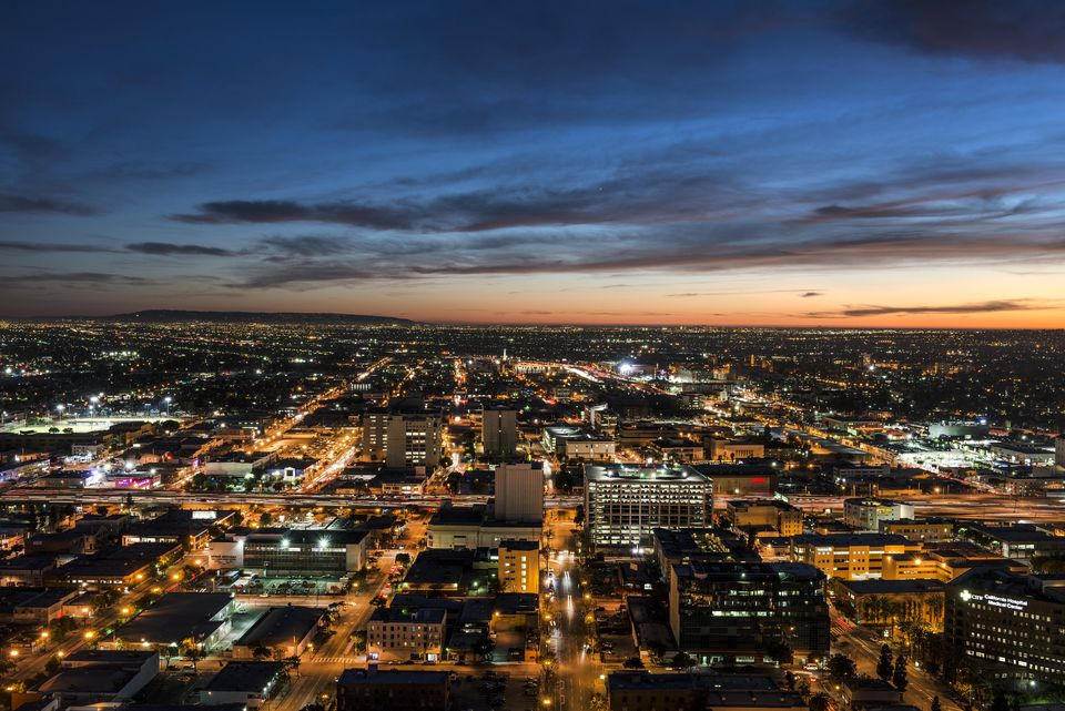 Nighttime skyline view of Los Angeles, California, looking west toward the setting sun