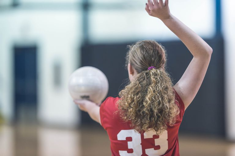 high school girl serving volleyball