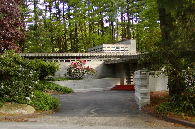 Driveway to decorative concrete home, clerestory windows, wooded landscape