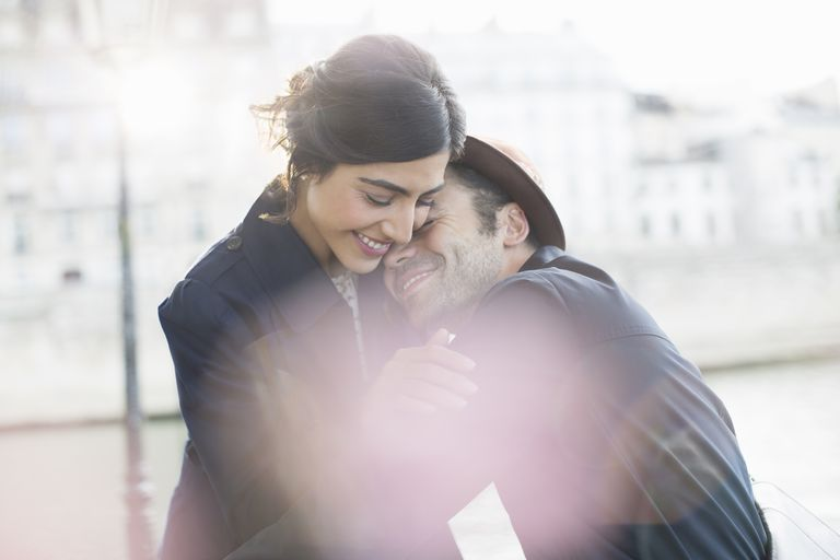 Couple hugging along Seine River, Paris, France - during ovulation, sexual attraction is higher