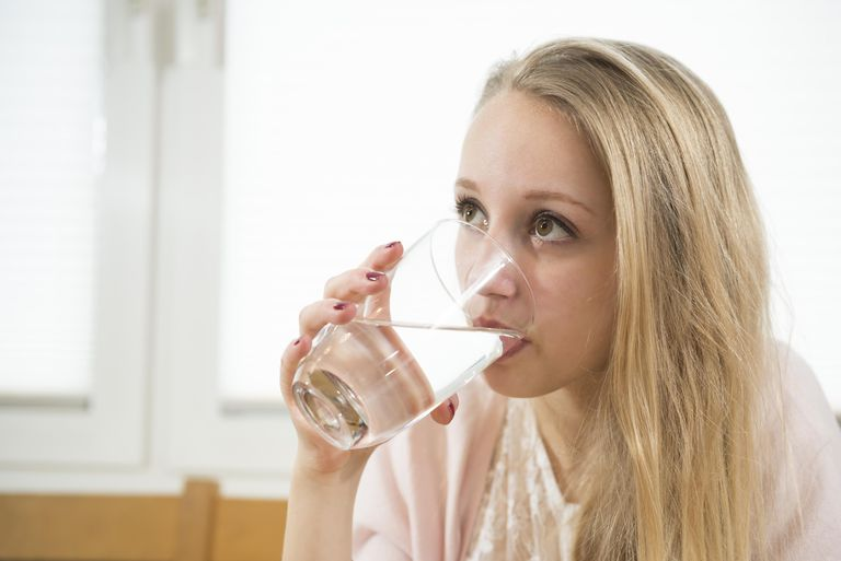 Germany, Munich, Teenage girl drinking water, close up