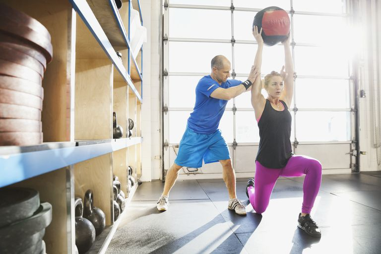 Gym instructor assisting woman with medicine ball lunge