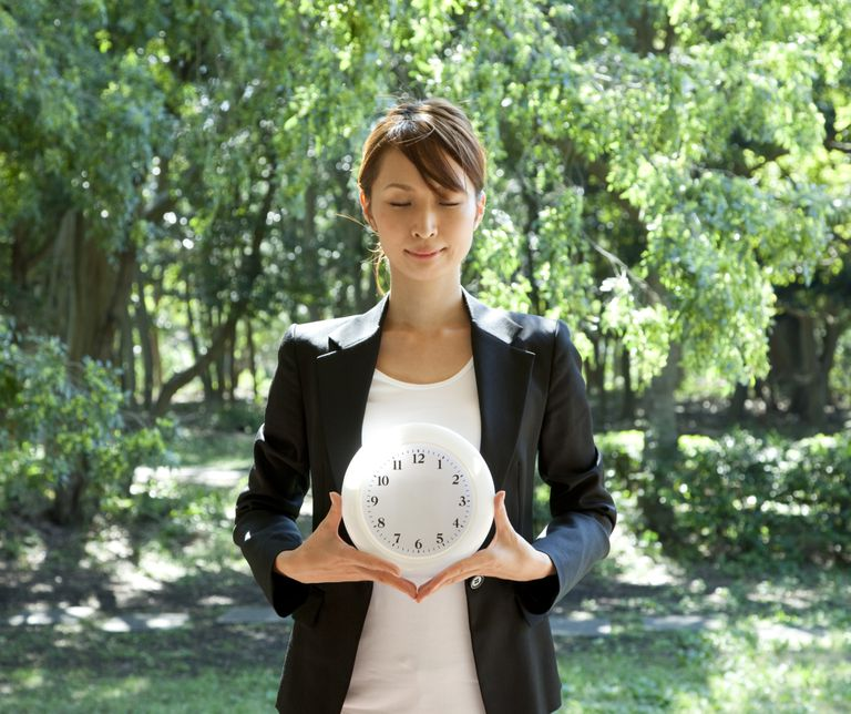Woman standing with handless clock, comtemplating when to have kids