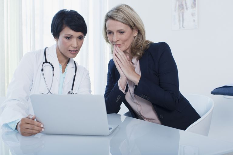 Female doctor and patient using laptop in hospital office