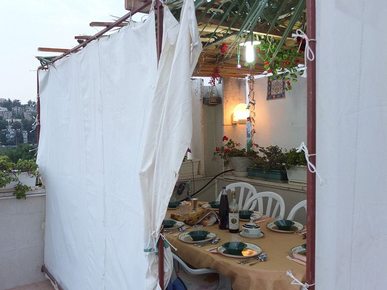 Canvas-sided sukkah on a roof in Jerusalem topped with palm branches and bamboo mat.