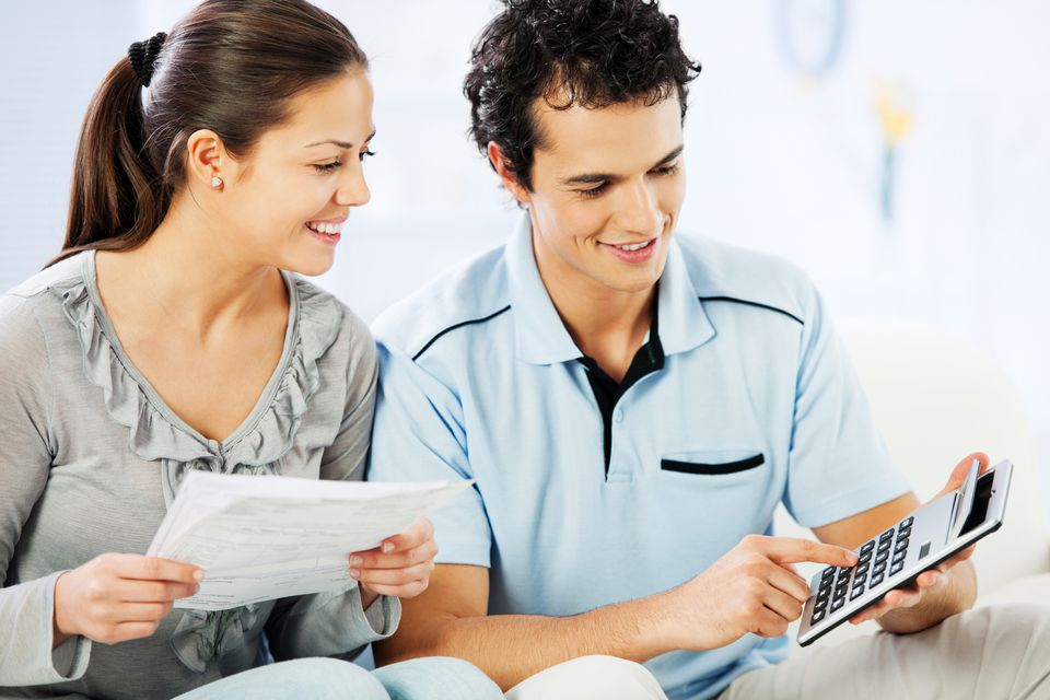 Young cheerful couple doing their taxes.
