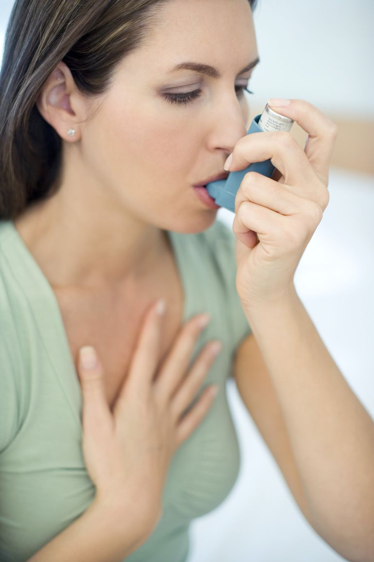 Woman using inhaler to treat asthma attack