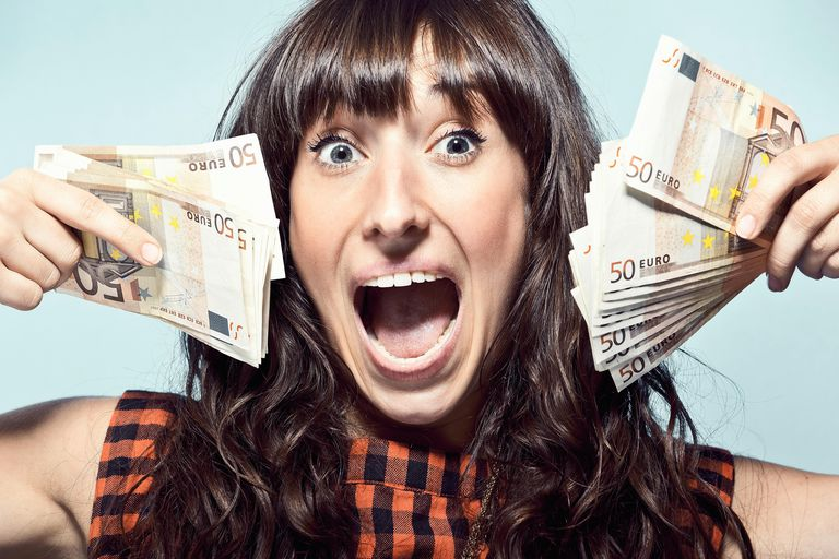 An excited woman holding lots of money bills in her hand