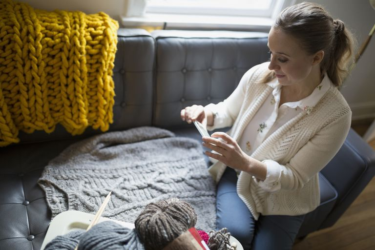 Woman taking photo of sweater to sell online