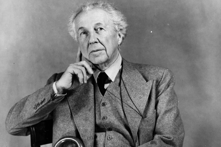Black and white portrait of Frank Lloyd Wright, an older white man sitting in a chair, with a cane, dressed in a three-piece suit, with his large hand up to his face