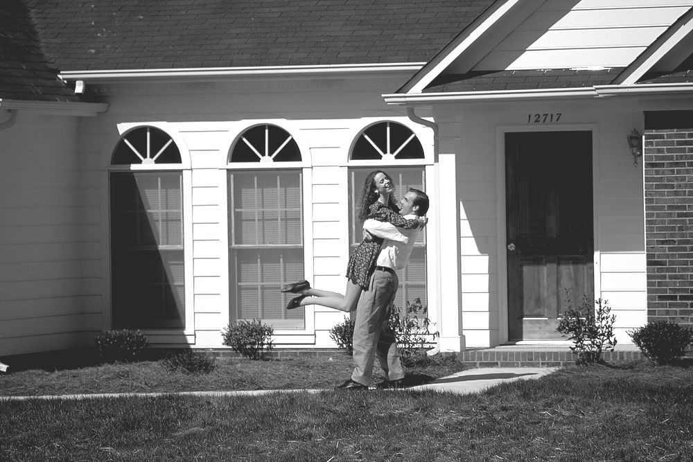 Couple embracing outside newly approved home