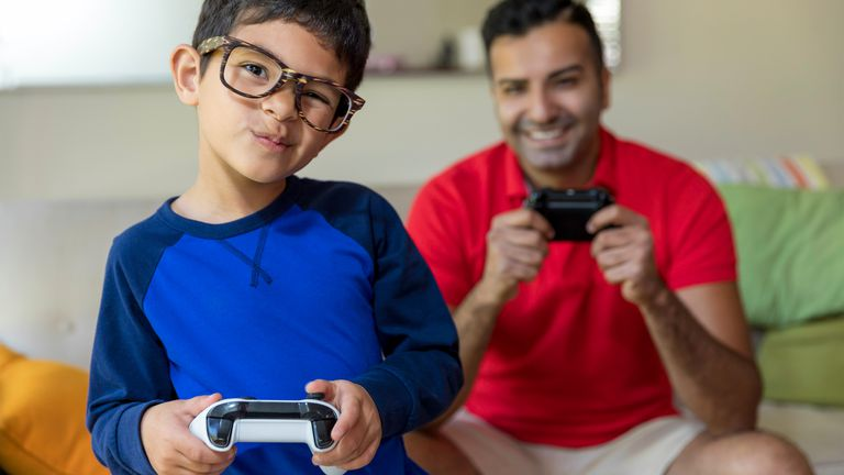 Boy and father playing Xbox One video games