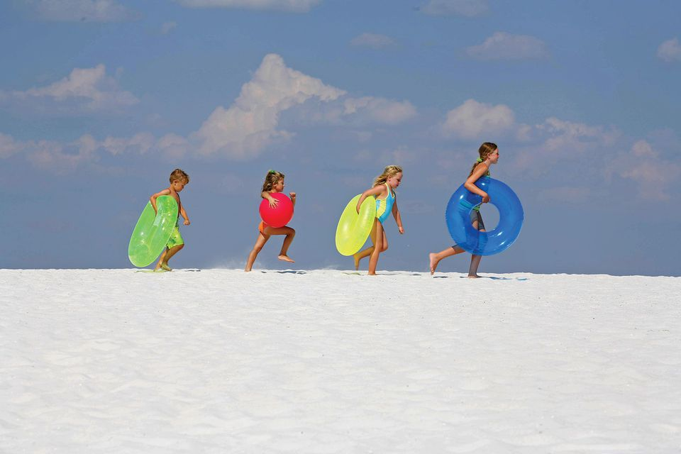 Kids marching to the water along the white sands of Panama City Beach