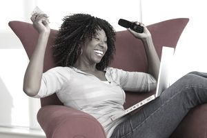 Woman sitting in red chair with credit card, laptop, and mobile phone