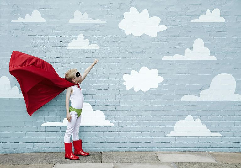 Niño celebrando el día del niño con capa de super héroe