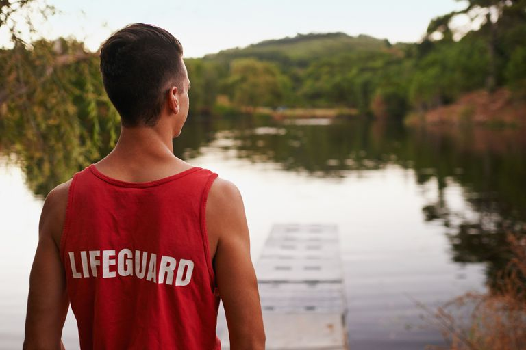 teen boy lifeguard looking over lake