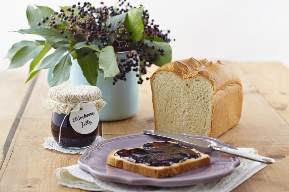Elderberry jam with white bread on wooden table