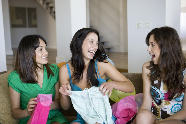 Girl opening birthday gift with two friends