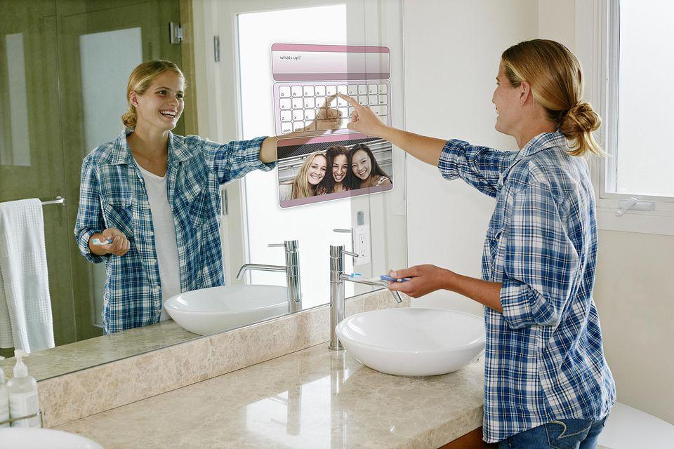 woman using computer on bathroom mirror