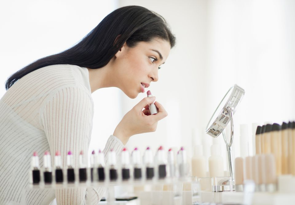 Woman testing lipstick at a department store makeup counter