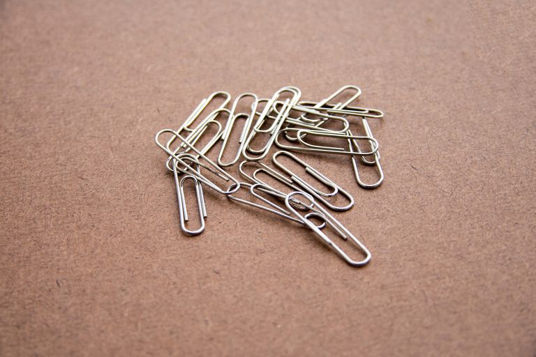 Close-Up Of Paper Clips On Brown Table