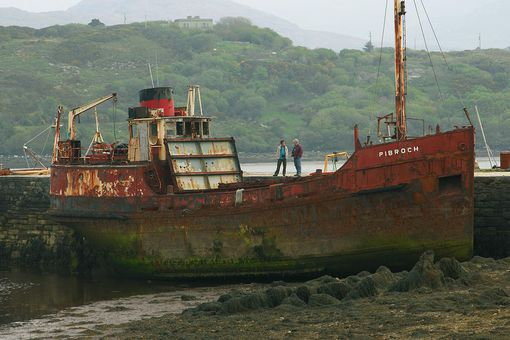 A Small Freighter Ship Sits Aground Next to a Stone Wharf