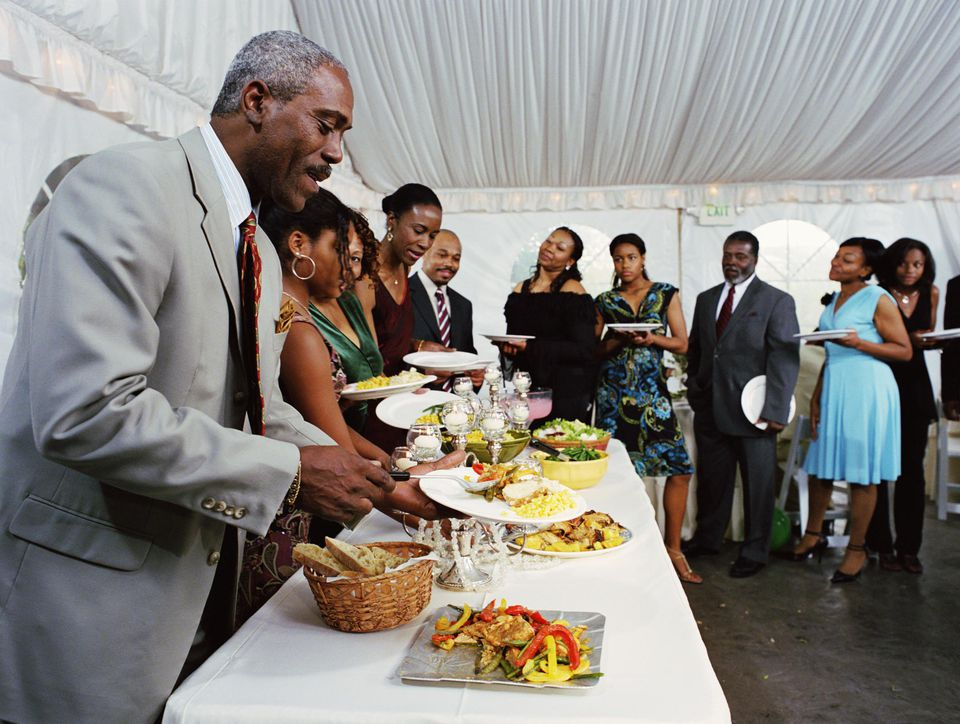 Family lining up to fill plates at buffet table at celebration
