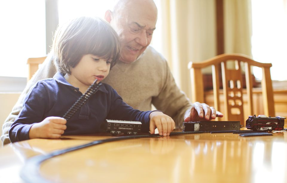 Grandfather playing with model trains with his grandson