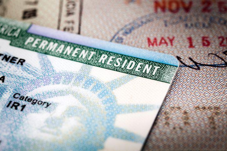 A Green Card lying on an open passport, close-up, full frame