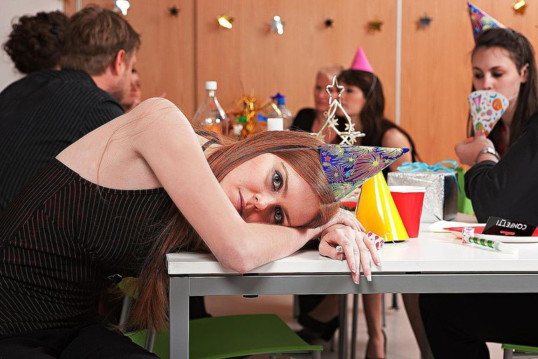 A woman sitting alone and looking bored at a party where others are having fun symbolizes social alienation.