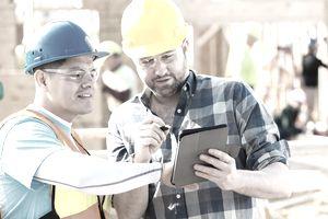 Construction foremen review plans on digital tablet
