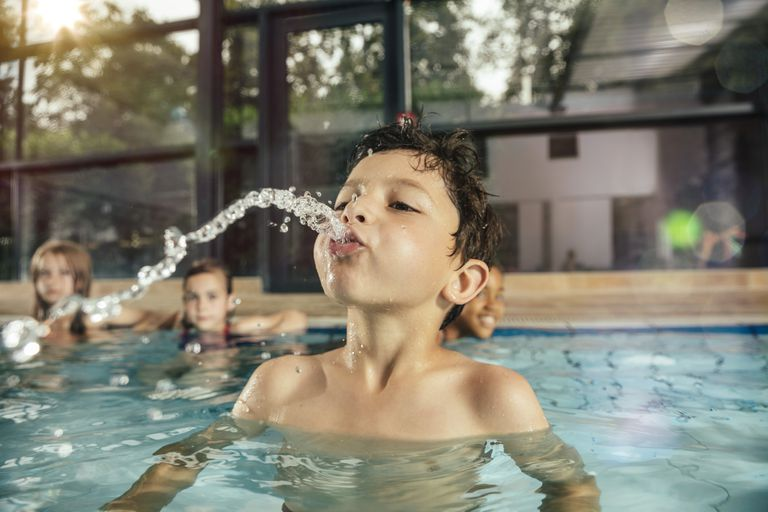 Boy with friends in indoor swimming pool spitting water