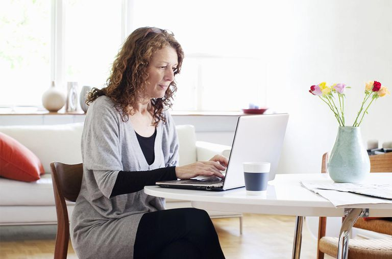 Woman working on computer, home.