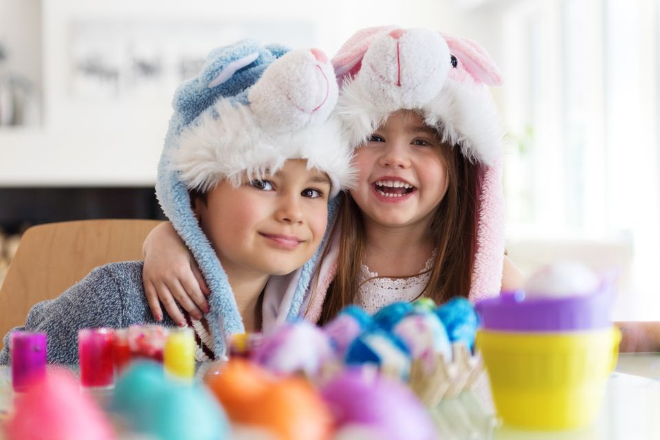 Little boy and girl painting easter eggs
