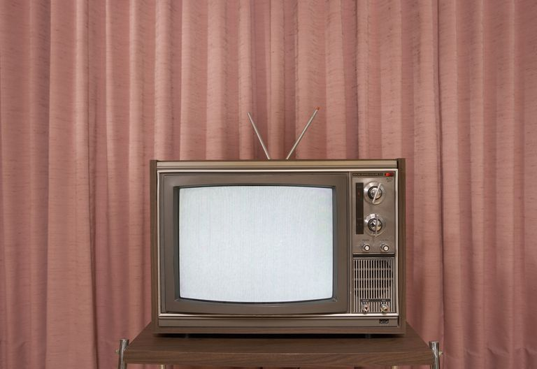 Old television on stand, in front of curtain