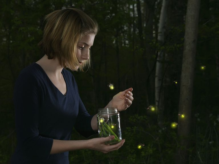 Girl holding jar of illuminated fireflies